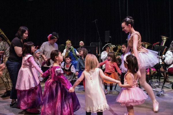 Ballerina teaches a group of children a ballet dance