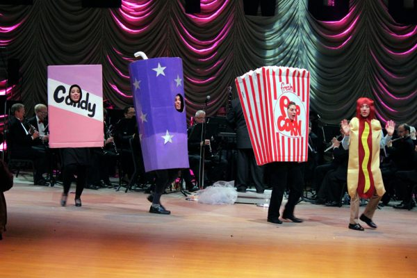 Show's cast dressed as life-size candy, soda, popcorn and a hot dog come out singing and dancing