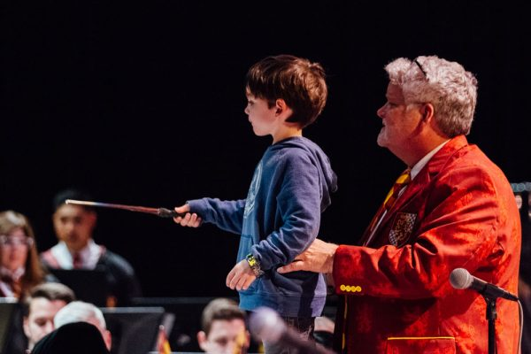 A young guest conductor stands on a chair and keeps the band playing perfectly in time
