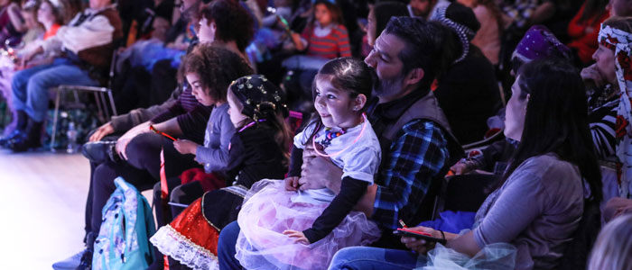 A family sits in the front row watching the Dance-Along Nutcracker actors perform